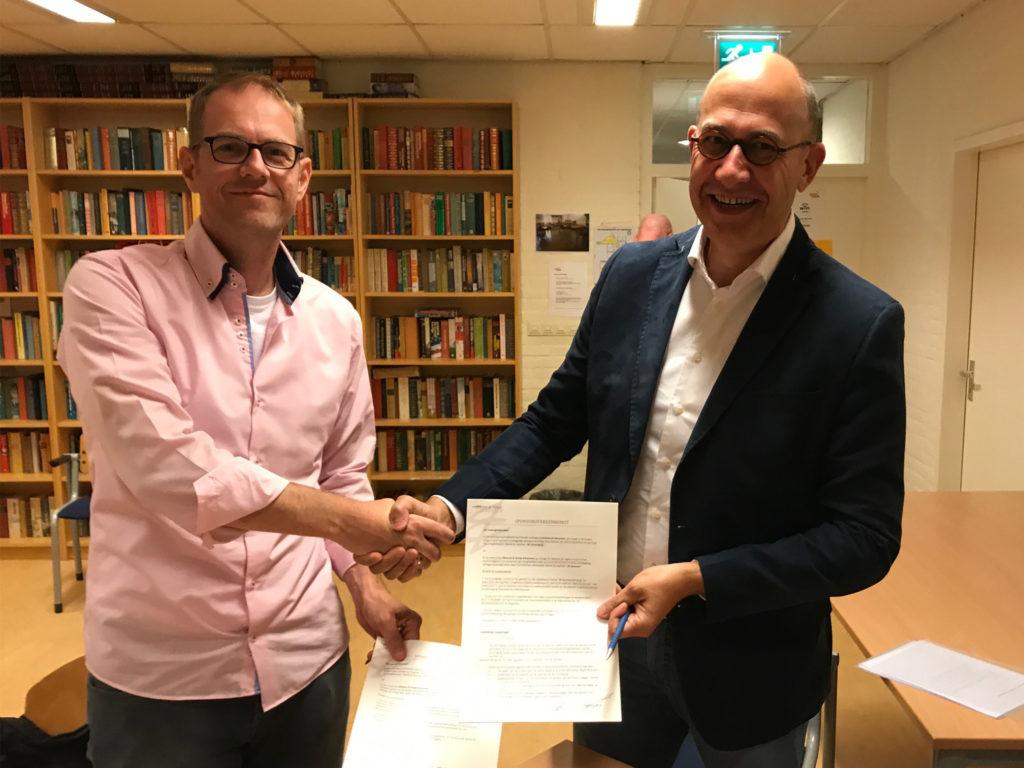 Marcel van Oort in zijn nopjes met het getekende contract, samen met Hans Tuit.